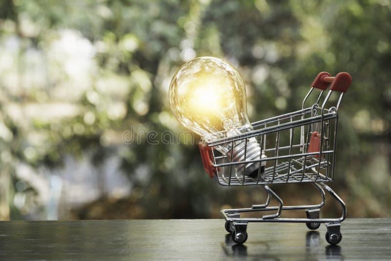 Energi - ljus kula för besparing med shoppingvagnen som är finansiell och shoppar begrepps- och kopieringsutrymme för mellanläggs arkivfoton