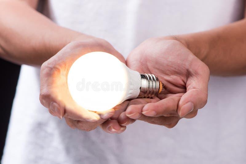 Energi - sparande ljus kula, idérik idé för ljus kula i handen royaltyfri fotografi