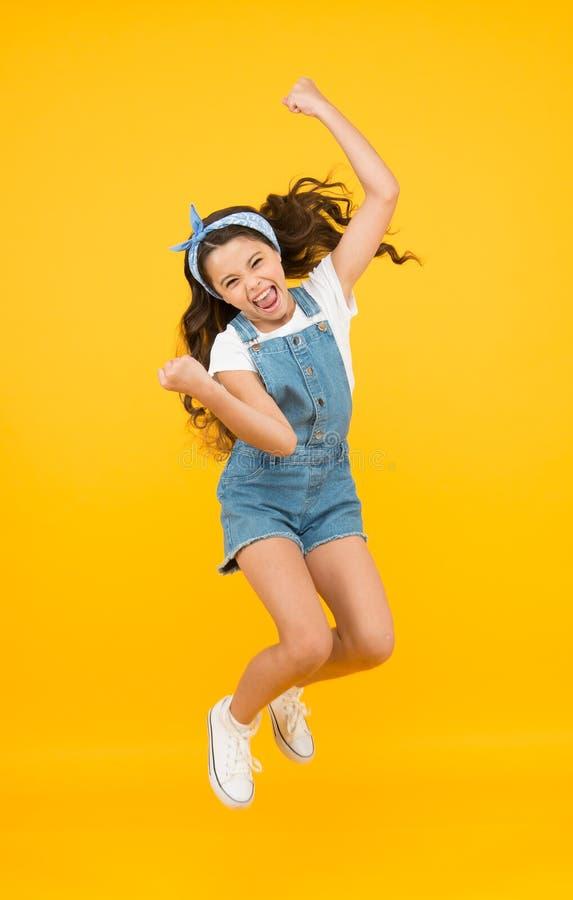 Energia all'interno Sentirsi liberi Carefree vacanze estive Salto della felicità Ragazza piccola in fondo al giallo Godere fotografia stock