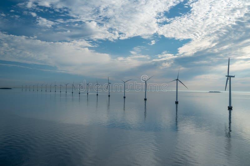 Energia alternativa do parque a pouca distância do mar do moinho de vento moinhos de vento no mar com reflexão na manhã, Dinamarc fotografia de stock