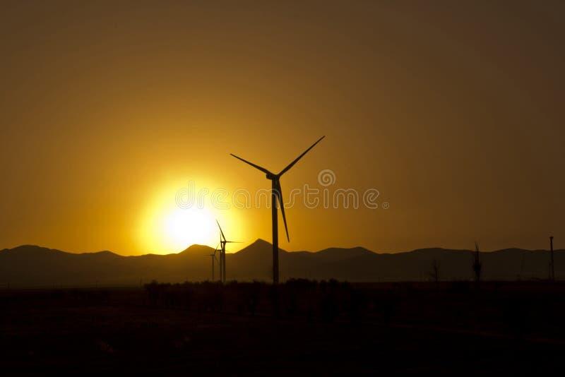 Energia eolica moderna della turbina o del mulino a vento nel tramonto fotografia stock libera da diritti