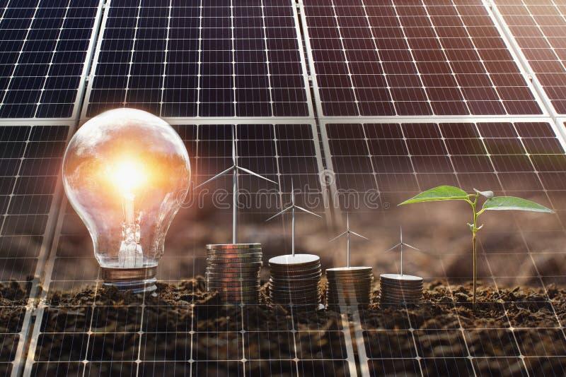 energia pulita di concetto e potere di risparmio in natura pannello solare con il turebine del vento su soldi e sulla lampadina fotografia stock libera da diritti