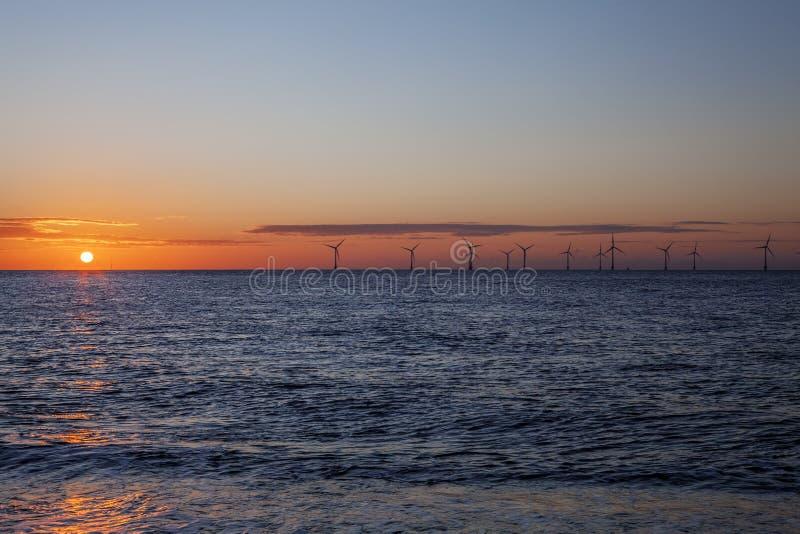 Energia renovável - exploração agrícola de vento a pouca distância do mar no alvorecer fotos de stock royalty free