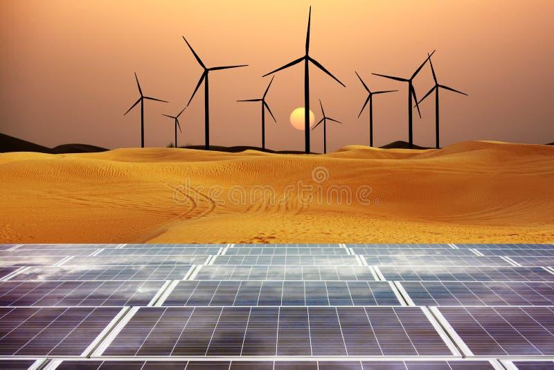 Energia rinnovabile con i mulini a vento ed i pannelli solari in dessert al tramonto fotografie stock