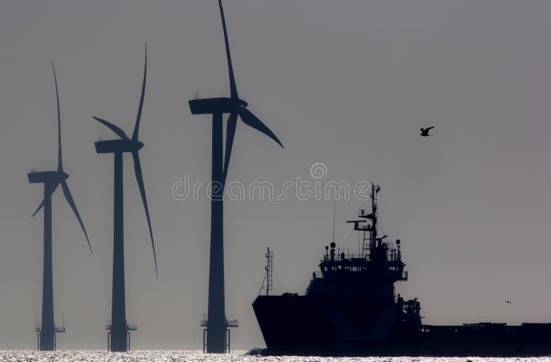Energia verde Turbinas da exploração agrícola de vento a pouca distância do mar com o navio no mar Silh imagem de stock
