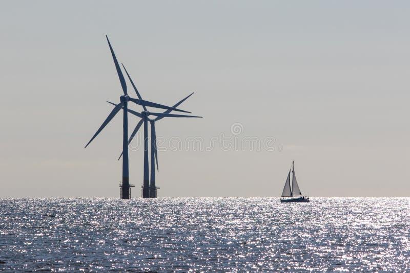 Energias e?licas Iate de navigação a favor do meio ambiente Turbinas a pouca distância do mar do windfarm Energia limpa fotos de stock