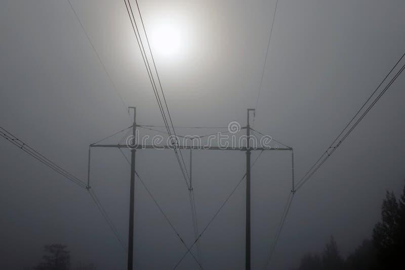 Energie, steun voor machtslijnen met hoog voltage bij zonsopgang in de ochtendmist stock foto's