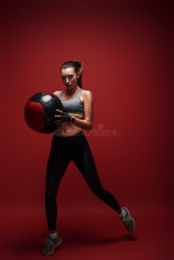Energie und Schönheit Die Sportlerin springend mit einem Ball über rotem Hintergrund lizenzfreie stockfotos