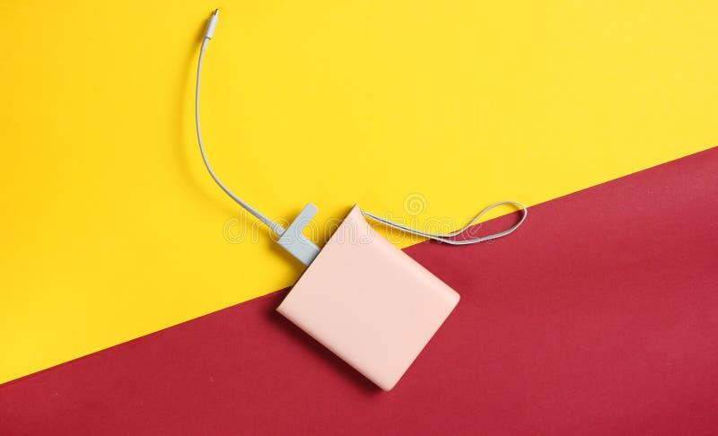 Energiebank mit usb-Kabel auf einem gelben roten Papierhintergrund, Draufsicht lizenzfreie stockbilder