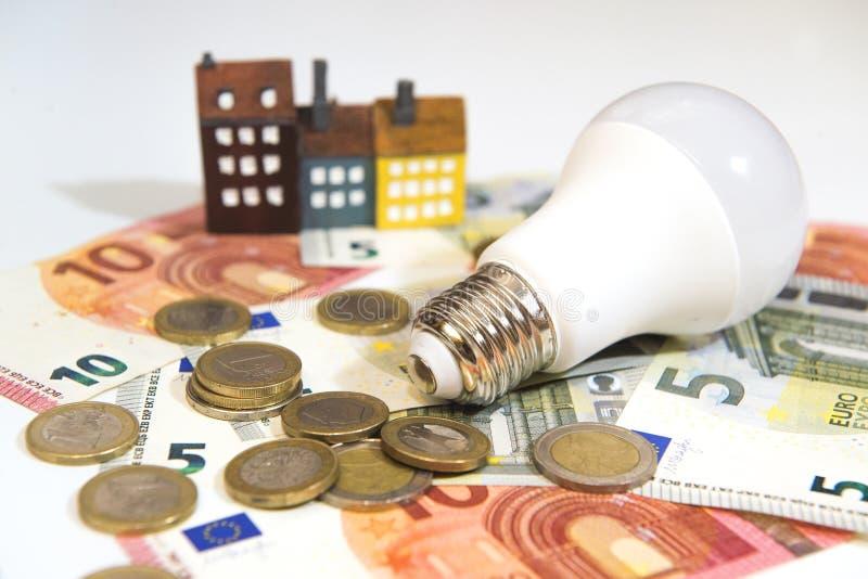 Energieeinsparung in einem Haus und Geld in einer Glühbirne lizenzfreies stockfoto