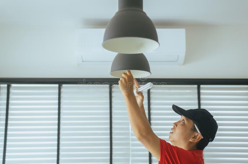 Energieeinsparung elektrisch und Leistungsfähigkeits-Konzept, kompakt-Leuchtstoff CFL Birne des Handtechnikers mit neuer Glühlamp stockbilder