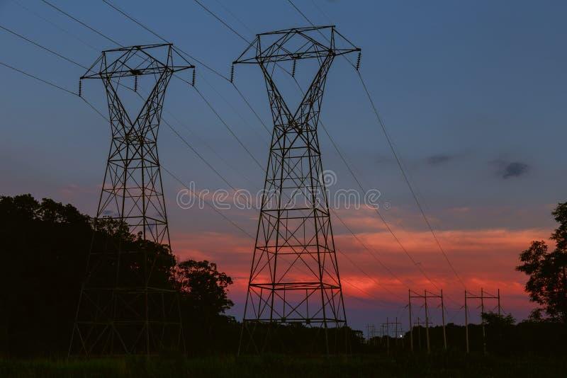 Energiefreileitungsmast silhouettiert gegen Abendrot lizenzfreies stockbild