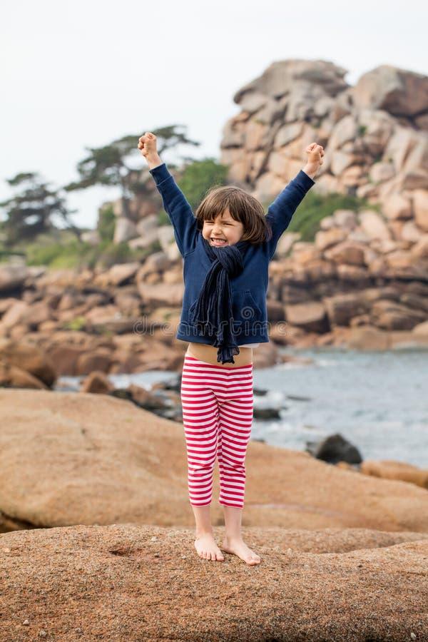 Energiek jong kind die zijn wapens voor vrijheid en overwinning uitrekken royalty-vrije stock afbeeldingen