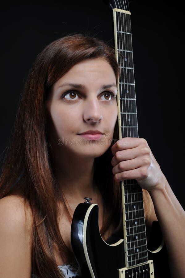Energiek meisje met een zwarte gitaar in zijn hand. stock afbeelding