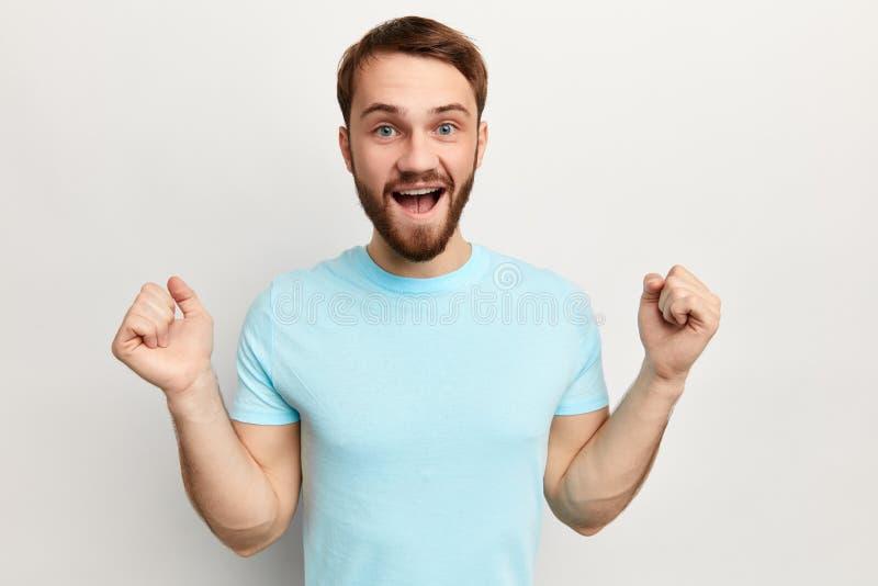 Energieke jonge positieve bedrijfsmens die van succes genieten stock foto's
