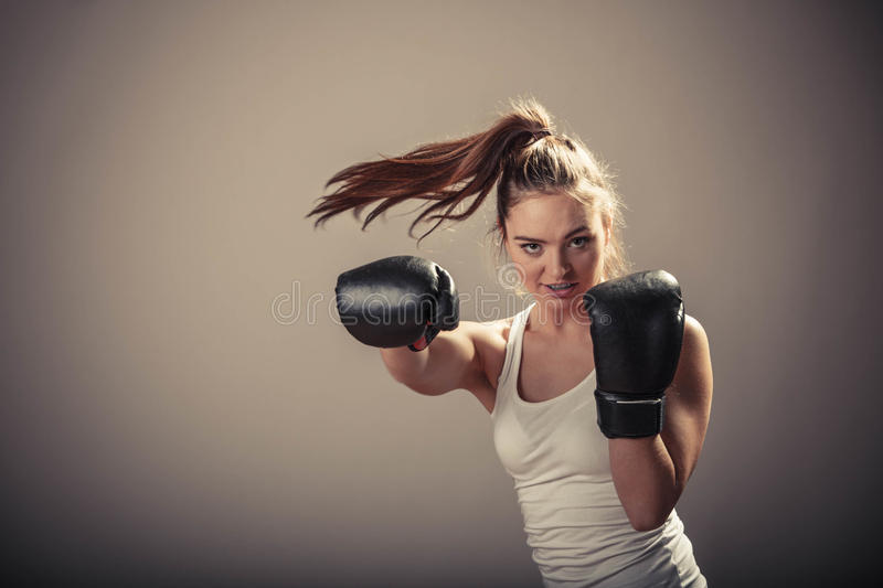 Energieke jonge vrouwenstrijd met bokshandschoenen royalty-vrije stock foto's
