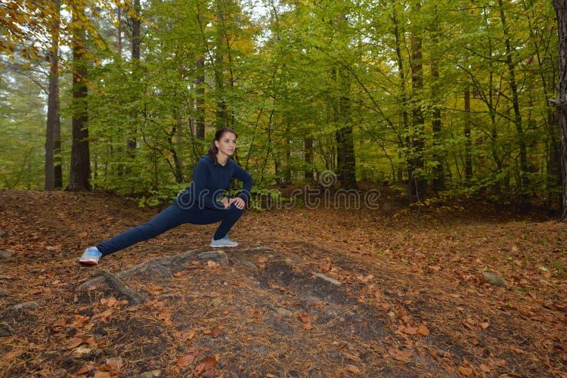 Energieke jonge woman do exercises in openlucht in park om thei te houden royalty-vrije stock afbeelding