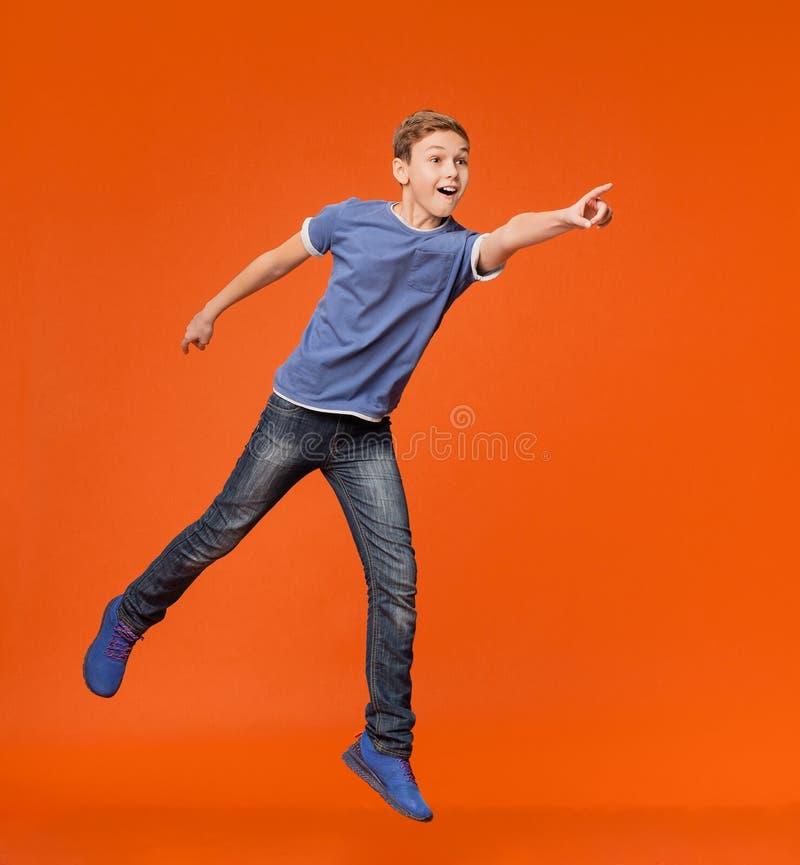 Energieke jongen die en hand opzij springen richten aan lege ruimte royalty-vrije stock foto