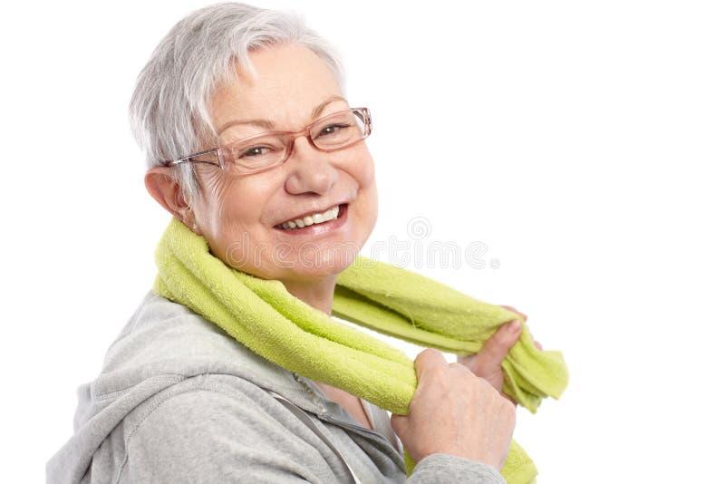 Energieke oude vrouw die na training glimlacht royalty-vrije stock foto's