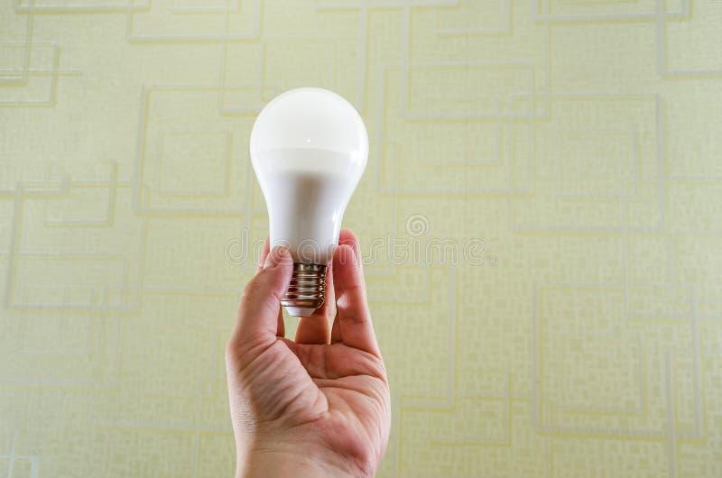 Energiesparende Glühlampe in der Hand lizenzfreies stockfoto