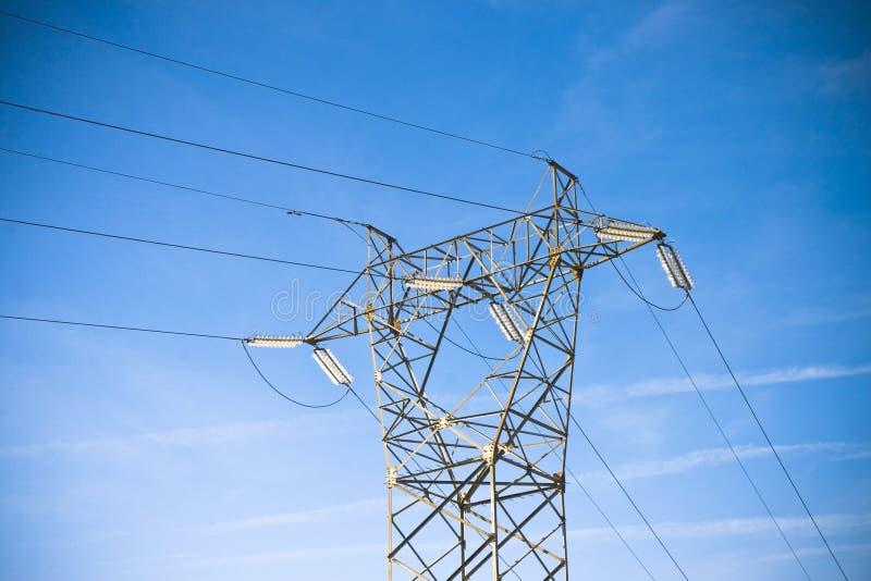 Energieturm und -Fernleitungen auf blauem Hintergrund stockbild