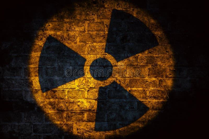 Energii atomowej napromieniania promieniotwórczego jonizacyjnego atomowego round symbolu żółty kształt malujący na cegła betonu c zdjęcia royalty free