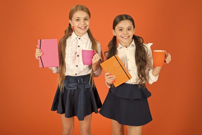 Energize seu dia Estudantes bonitos que guardam copos e livros Pouco crian?as que bebem o ch? ou o leite da manh? escola fotografia de stock royalty free