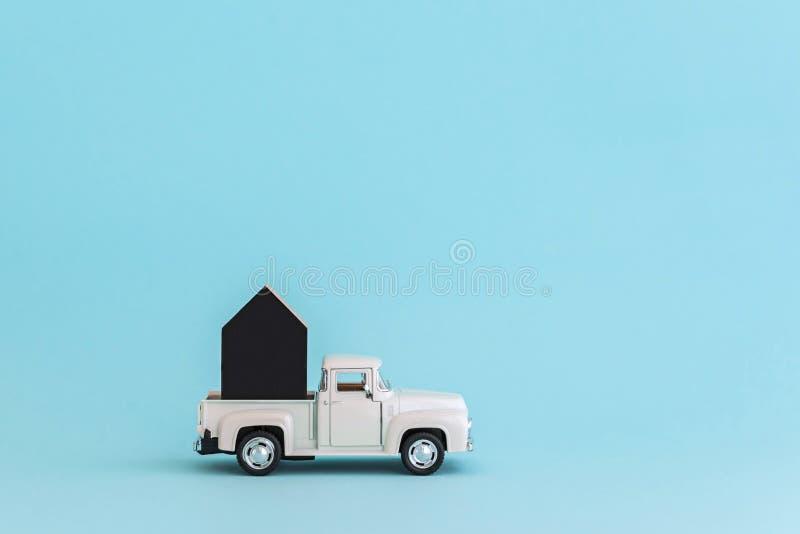 ENERGODAR, de OEKRAÏNE - Januari, 2019: Zwart houten die stuk speelgoed huis op witte stuk speelgoed auto wordt geladen - Beeld stock foto's