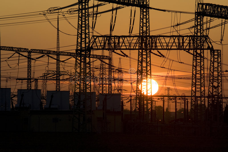 Energy. Solar energy versus electrical energy - sunset and network system of high voltage royalty free stock image