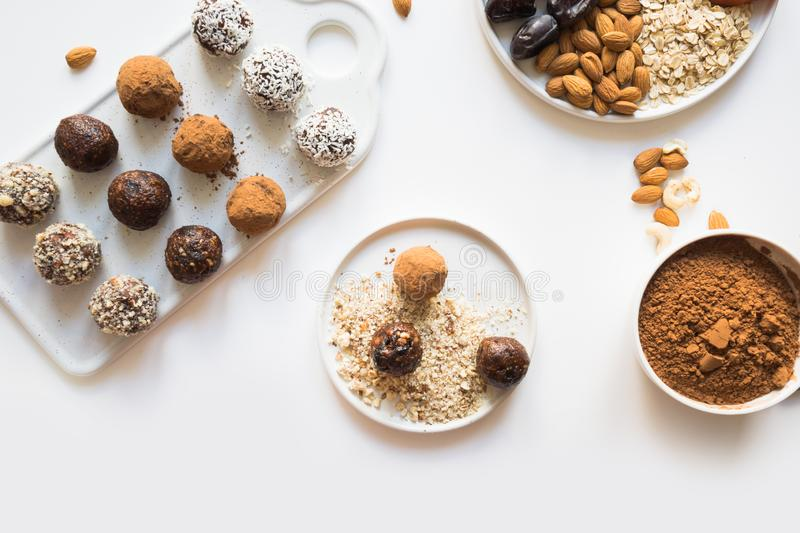 Energy balls with cacao and nuts on white. Healthy food for children and vegan. Energy balls with cacao and nuts on white. Prepare treat. Healthy food for royalty free stock image
