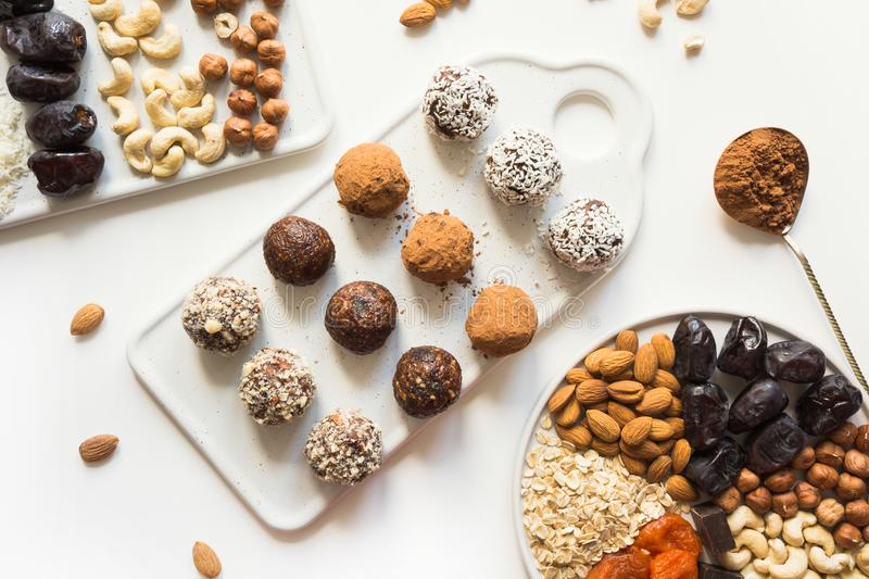 Energy balls with cacao and nuts on white. Healthy food for children and vegan. Energy balls with cacao and nuts on white. Prepare treat. Healthy food for royalty free stock photography