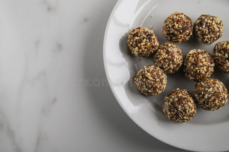 Energy balls – homemade healthy dessert cooked with dates, nuts, dry fruits and cocoa. Organic dry fruits snacks on marble background stock photography