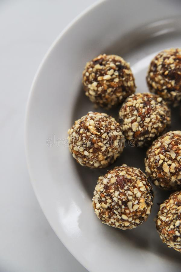 Energy balls - homemade healthy dessert cooked with dates, nuts, dry fruits and cocoa. Organic dry fruits snacks on marble background royalty free stock photography