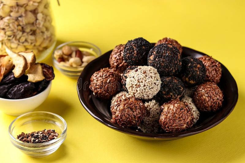 Energy balls and ingredients: nuts, oatmeal and dried fruits on a plate on yellow background, horizontal orientation. Close up royalty free stock photography