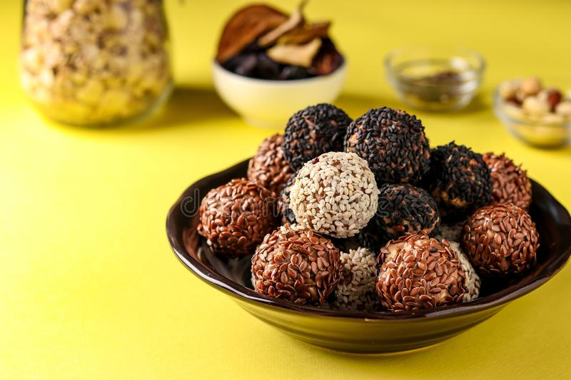 Energy balls and ingredients: nuts, oatmeal and dried fruits on a plate on yellow background, horizontal orientation. Close up stock photos