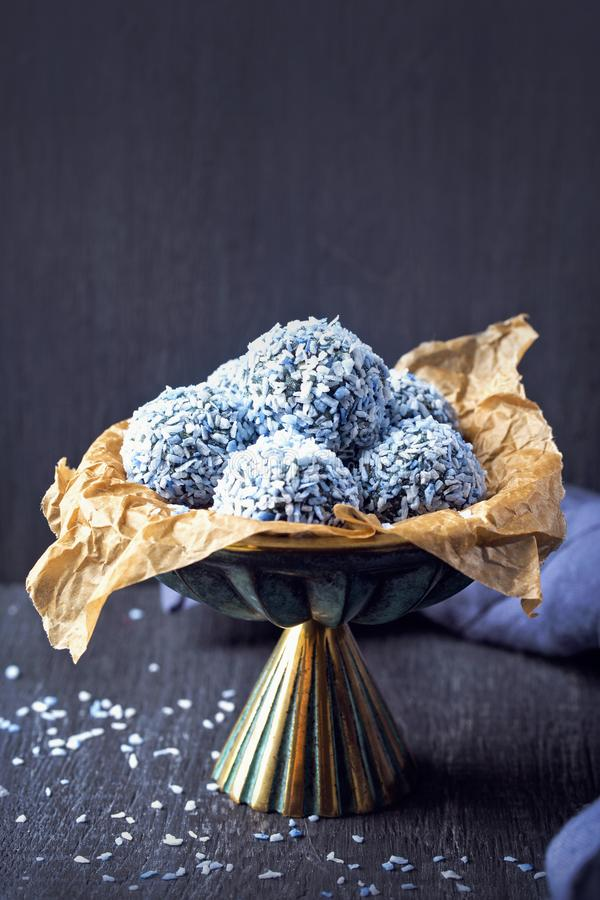 Energy balls with nuts, hemp hearts. Blue spirulina and shredded coconut stock photos