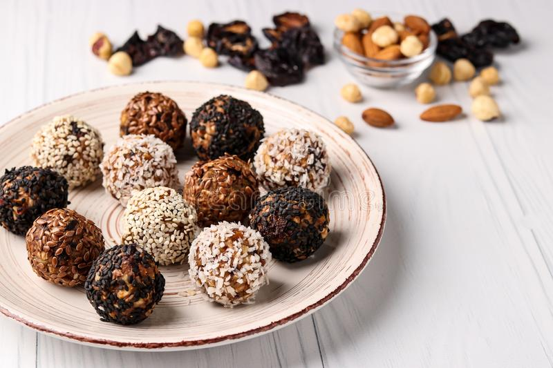 Energy balls of nuts, oatmeal and dried fruits on a plate on a white background, horizontal orientation. Close up stock photography