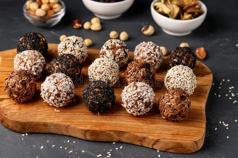 Energy balls of nuts, oatmeals and dried fruit on wooden board on dark background, horizontal orientation. Close up royalty free stock images