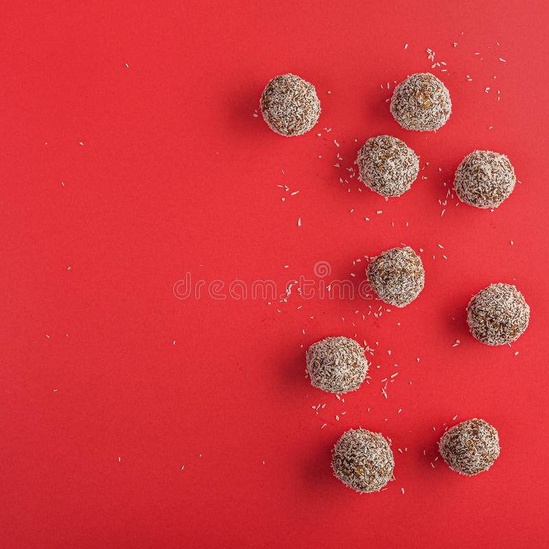 Energy bites for raw vegan diet , no bake. Healthy raw energy balls with cocoa, coconut, sesame, chia on a red background. Vegan chocolate truffles. Copy space stock photography