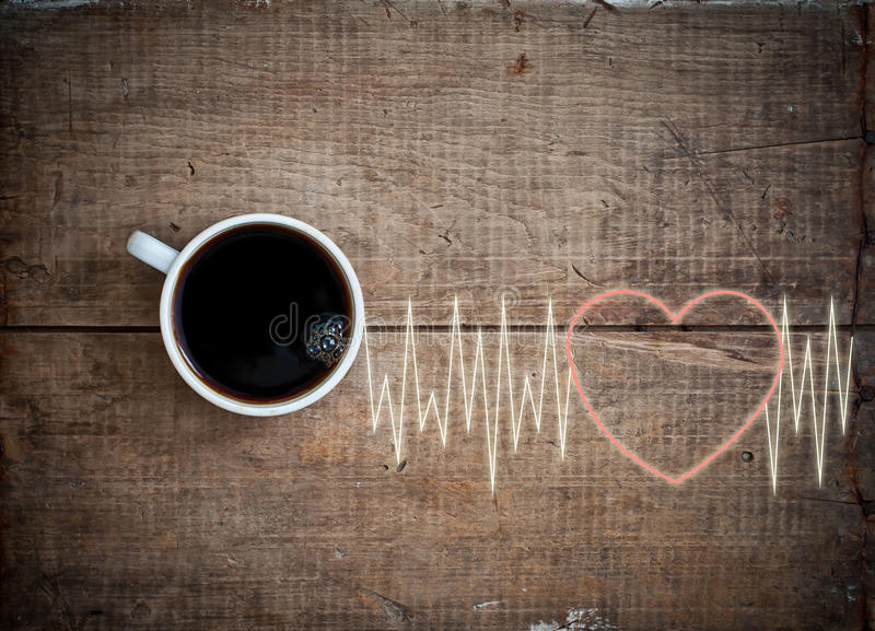 Energy cheerfulness with coffee. Heart beat cardiogram and black hot fresh coffee espresso in white cup on vintage grunge wooden background stock photo