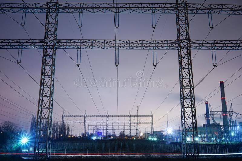 Energy of the city. Front view of rectangular structure of electric poles; Power plant, urban periphery High tension poles, transformation point; night scene royalty free stock photos