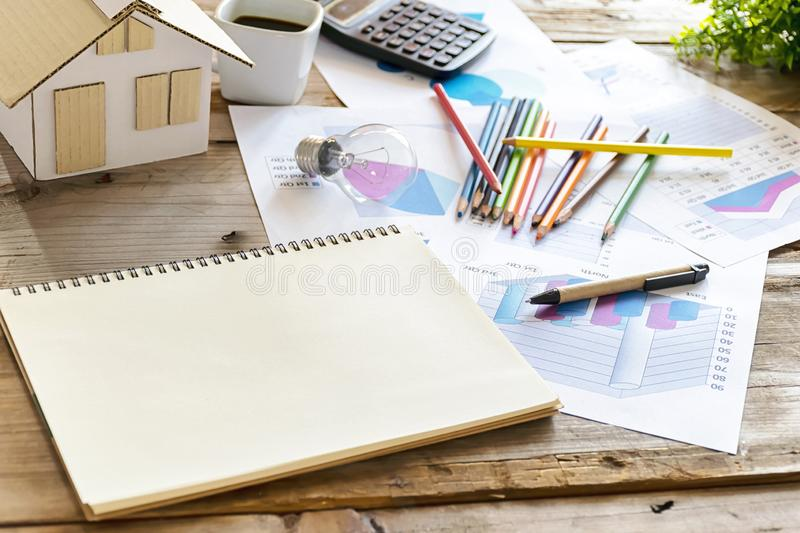 Energy concept, The desk has its place, house models, crayons, bulbs, coffee cup,calculator, Statistical documents, notebooks for stock photos