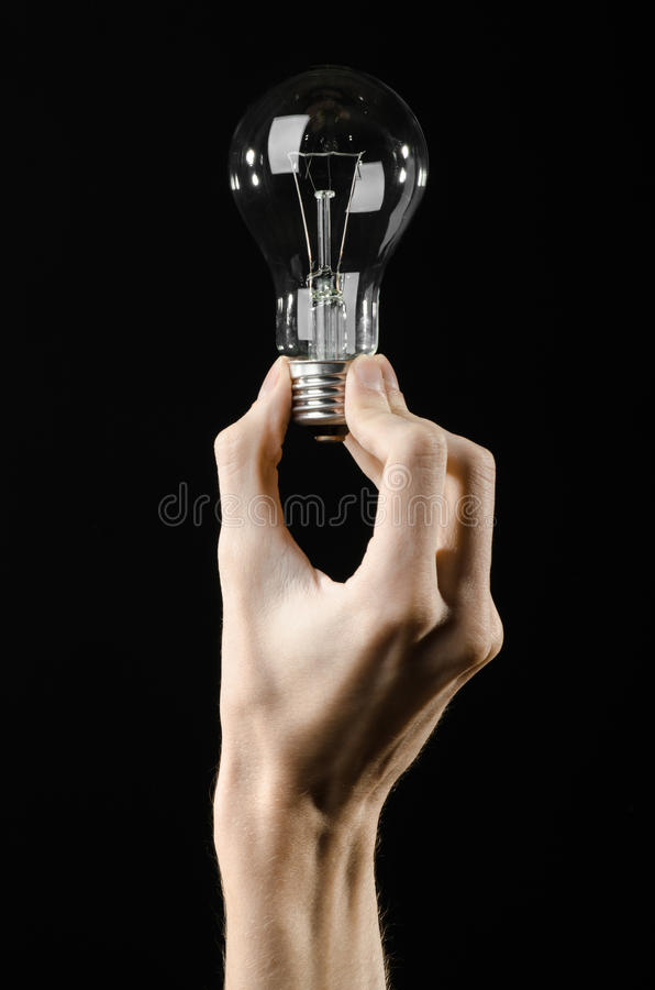 Energy consumption and energy saving topic: human hand holding a light bulb on black background in studio. Energy consumption and energy saving topic: human hand stock photos