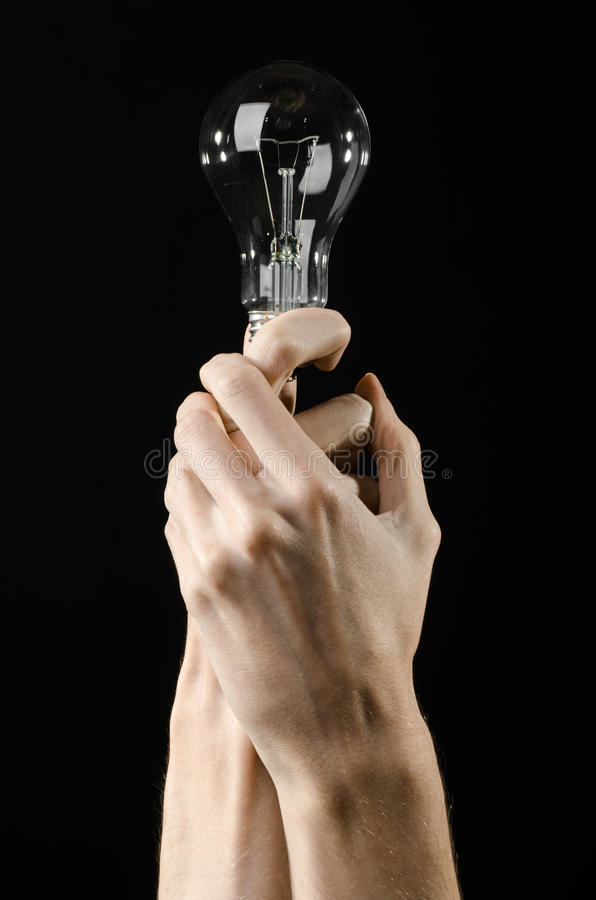 Energy consumption and energy saving topic: human hand holding a light bulb on black background in studio. Energy consumption and energy saving topic: human hand stock photo