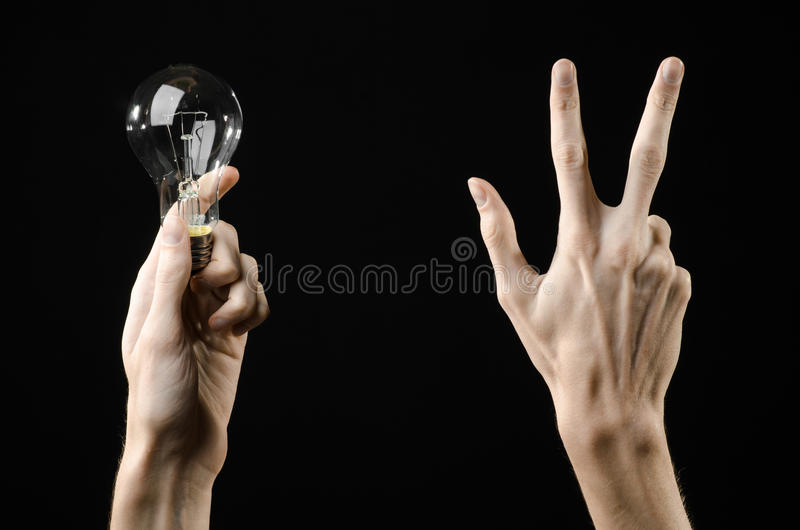 Energy consumption and energy saving topic: human hand holding a light bulb on black background in studio. Energy consumption and energy saving topic: human hand stock images
