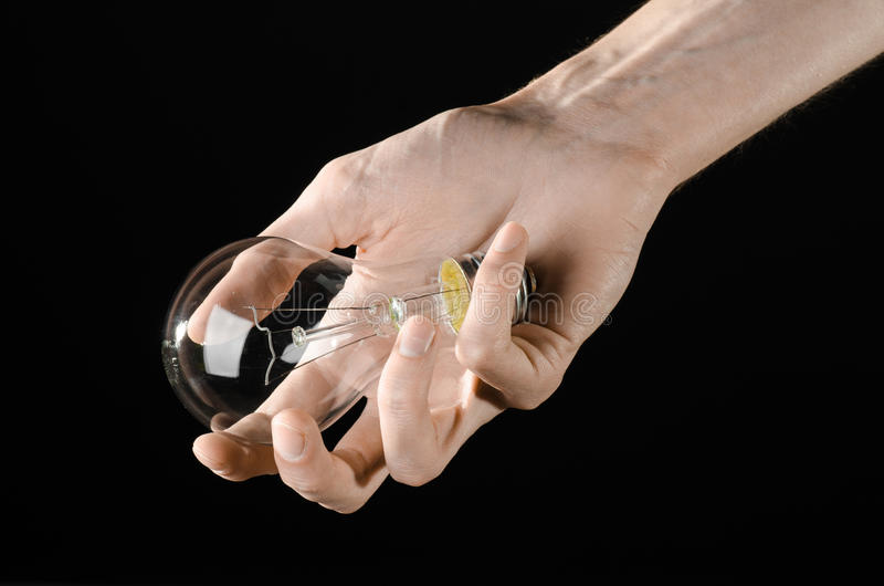 Energy consumption and energy saving topic: human hand holding a light bulb on black background in studio. Energy consumption and energy saving topic: human hand stock image
