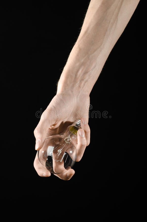 Energy consumption and energy saving topic: human hand holding a light bulb on black background in studio. Energy consumption and energy saving topic: human hand stock photography