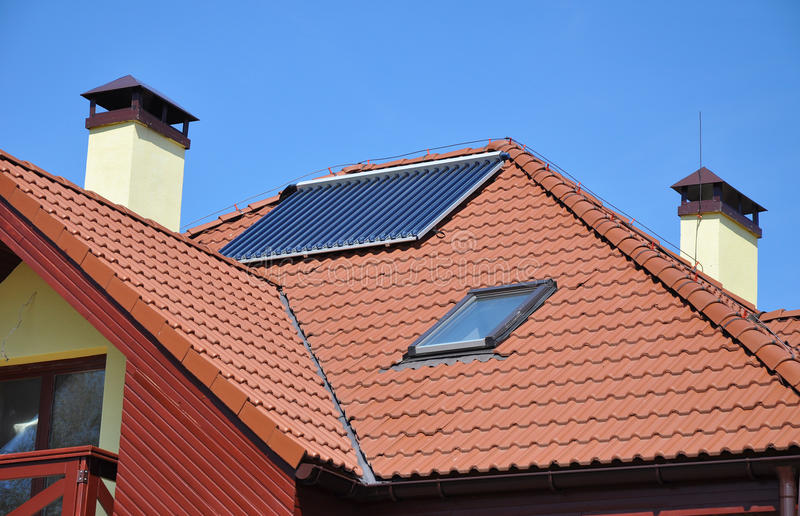 Energy efficiency concept. Closeup of solar water panel heating on red tiled house roof with lightning protection, skylights, stock photography