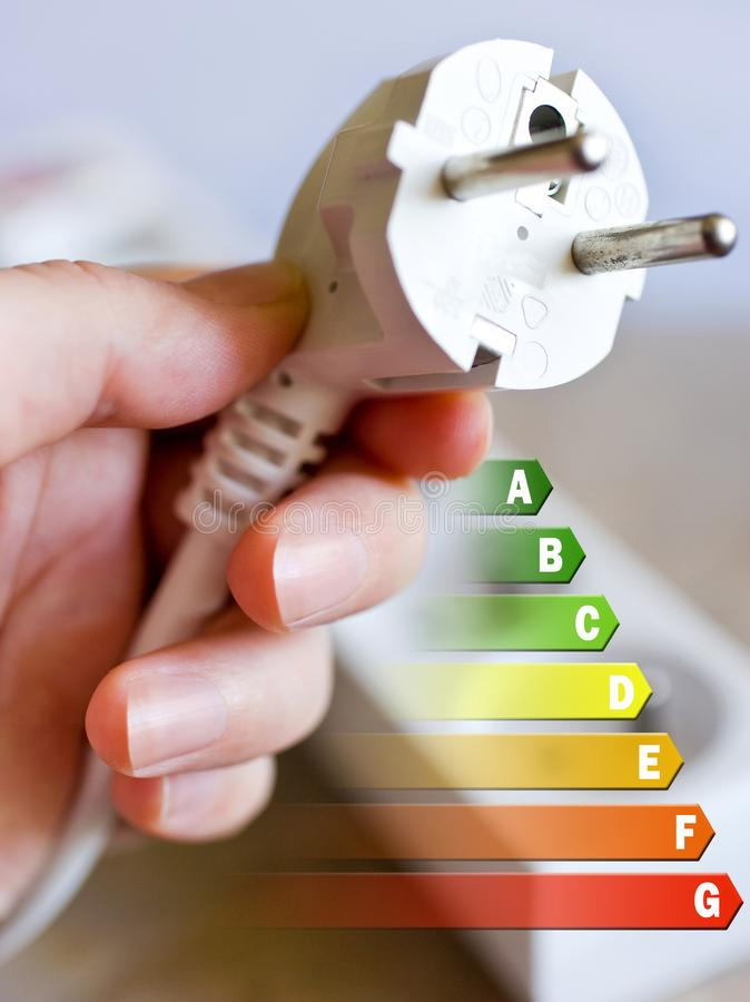 Energy efficiency label for house / electricity and money savings - plug in a hand royalty free stock photography