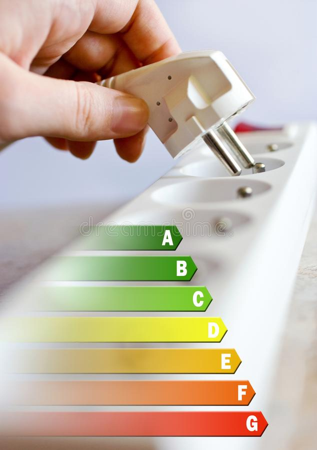 Energy efficiency label for house / electricity and money savings - plug in a hand. Over a socket stock photo
